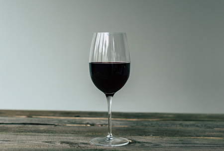 Glass of red wine on a wooden striped table 写真素材