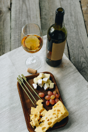 Glass with white wine and plate with cheese and grapes on a wooden striped tabletop