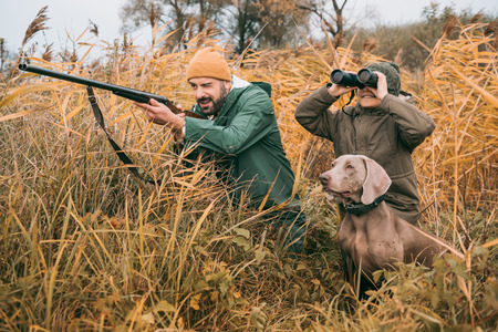 Father and son sitting in a bushes and hunting down an animal