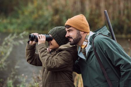 Sohn schaut durch ein Fernglas, Vater steht mit einer Waffe