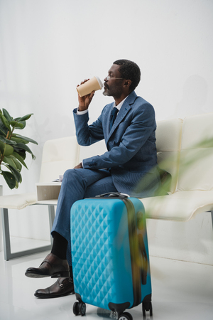 African american businessman drinking coffee while waiting for departure at the airport