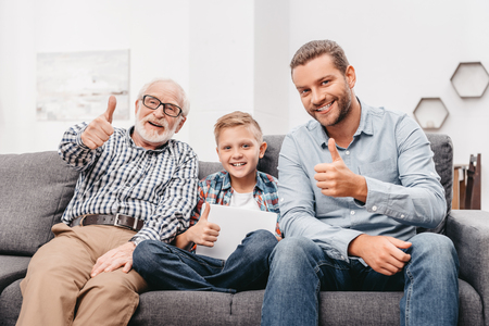 Father, son and grandfather sitting together on couch in living room and showing thumbs up