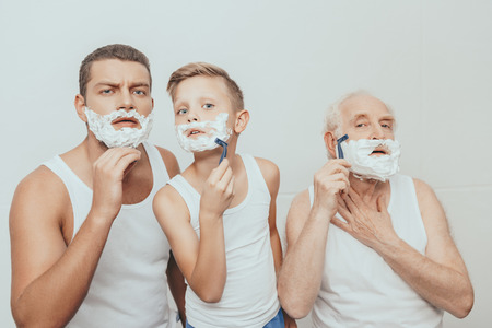 Father, son and grandfather standing with shaving cream on their faces shaving with razors, isolated on white