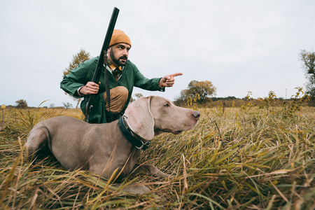 handsome man squatting with a dog and hunting down an animal  Stock Photo