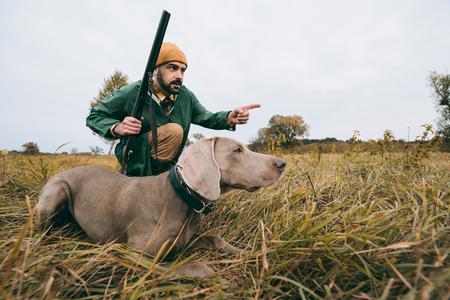 hombre guapo en cuclillas con un perro y cazando un animal Foto de archivo