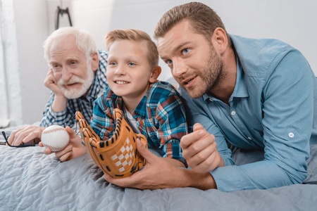 Little boy, his father and grandfather lying on the bed with baseball ball and mitt and watching a sports game Banco de Imagens