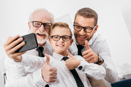 Father, son and grandfather wearing formal clothing and glasses taking a selfie with smartphone