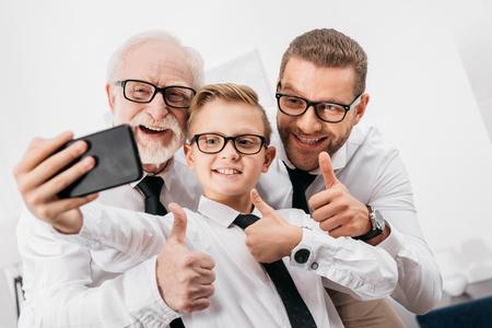 Padre, hijo y abuelo vistiendo ropa formal y gafas tomando un selfie con smartphone