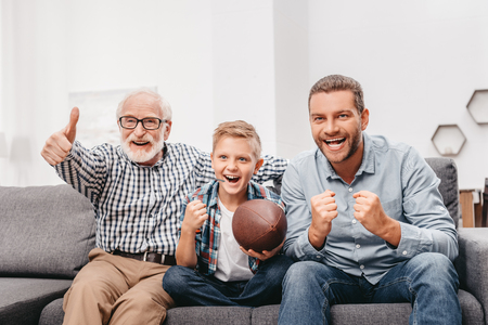 Little boy on couch with grandfather and father, cheering for a football game and holding a football ball Standard-Bild