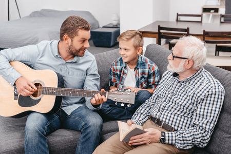 Young father playing guitar while little son and grandfather are watching him