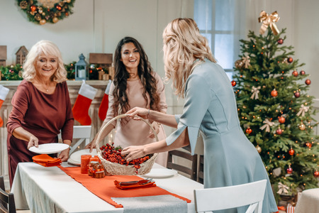 women decorating christmas table together with their senior mother