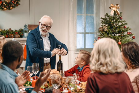 grandfather opening wine bottle on christmas dinner