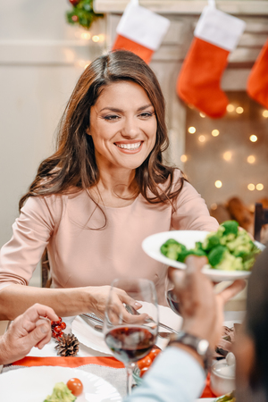 beautiful young woman with taking plate of broccoli from black man on christmas dinner