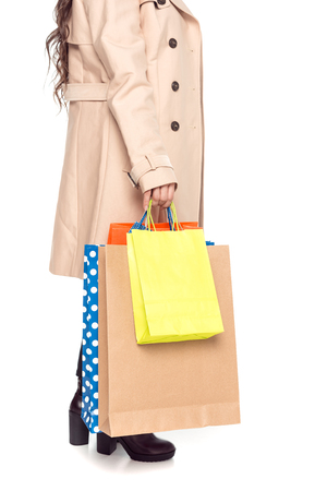 low section of woman holding shopping bags, isolated on white Stock Photo