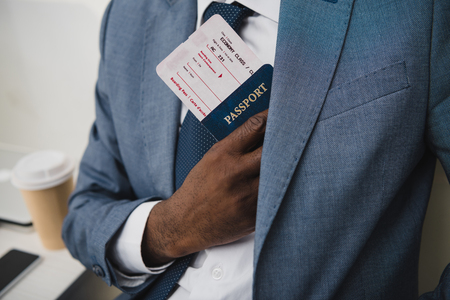 Cropped image of African american man hiding passport and fly ticket into pocket in suit