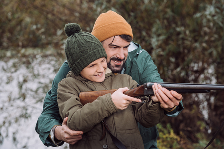 Father helping son aiming with a gun on a nature Stockfoto - 102617000
