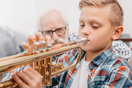 Little boy practicing playing trumpet while his grandfather is watching Stok Fotoğraf