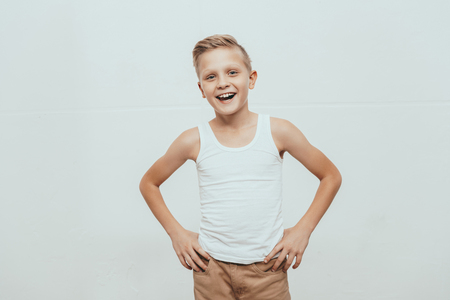 Young smiling boy in white tank top standing with hands on hips and looking at camera, isolated on white Stock Photo