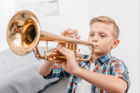 Young boy practicing playing trumpet in living room at home
