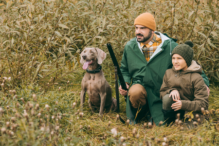 Father and son squatting in bushes with a dog and gun at hunt Stockfoto