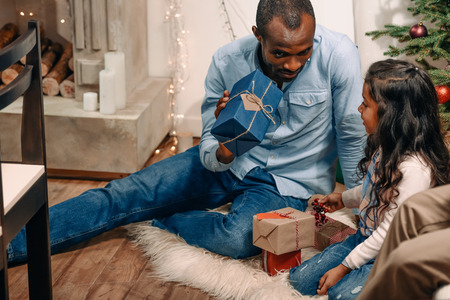 handsome african american father presenting christmas gift to daughter Stock Photo