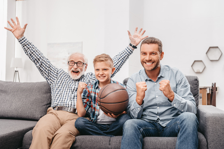 Little boy on couch with grandfather and father, cheering for a basketball game and holding a basketball ball Standard-Bild