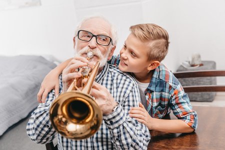 Grandfather playing trumpet while smiling boy is hugging him from behind