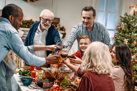 large beautiful family clinking glasses while having christmas dinner