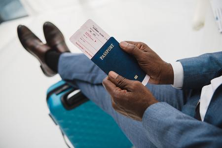 Przycięty obraz afroamerykańskiego mężczyzny trzymającego w rękach paszport i bilet lotniczy