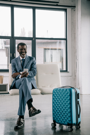 Middle aged African american smiling businessman waiting at airport and holding smartphone