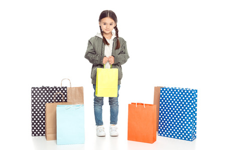 female kid holding shopping bags, isolated on white