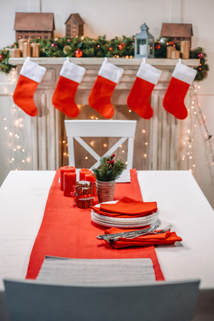 christmas table with tableware ready for serving in front of decorated fireplace 스톡 콘텐츠