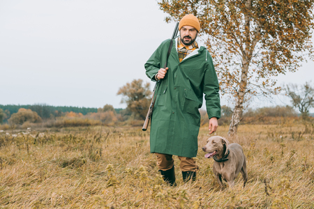 Handsome man walking with a dog and gun in a field  Stockfoto
