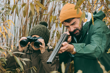 Father aiming at an animal with a gun, son looking through binoculars Stockfoto - 102617405
