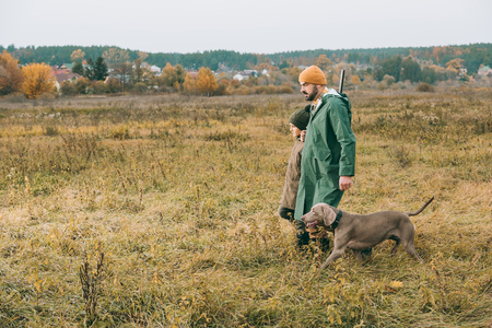 Father and son walking in a field with a dog and a gun
