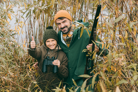Son showing thumb up while standing with father at hunt