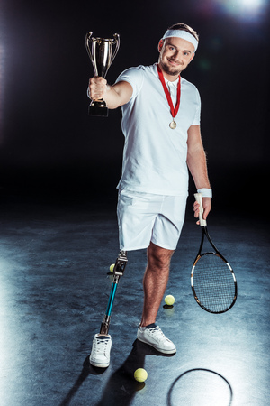 cheerful  tennis player looking at camera and showing champion goblet in hand Stock Photo