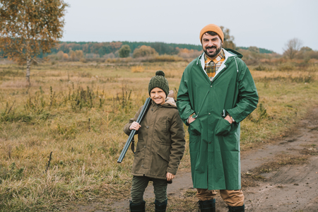 Father and son with a gun posing to camera on a nature