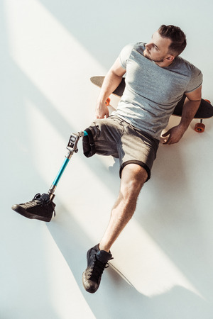 overhead view of pensive man with leg prosthesis resting on skateboarding isolated on white