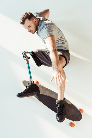 overhead view of young man with leg prosthesis with skateboard isolated on white Stockfoto