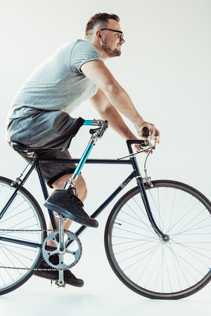 side view of  man in eyeglasses on bicycle isolated on white