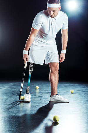 young  tennis player with leg prosthesis holding tennis racket