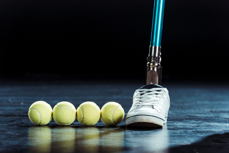 close up view of leg prosthesis and tennis balls