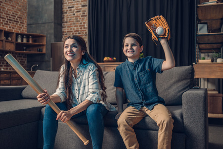 Little boy and his beautiful mother sitting on couch in living room with baseball bat and mitt, while watching tv