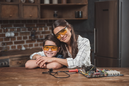Little son and his beautiful mother hugging while sitting at table with computer motherboard on it