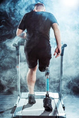 back view of sportsman with leg prosthesis training on treadmill