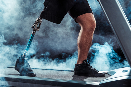 partial view of sportsman with leg prosthesis training on treadmill