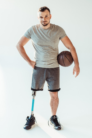 basketball player with basketball ball sanding akimbo isolated on white Stock Photo - 102637927