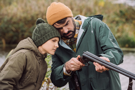 Father showing son how to load gun for hunt Stockfoto