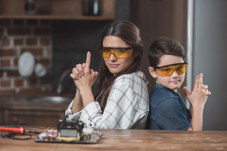 Little son and his beautiful mother wearing protective glasses posing and making gesture as if holding pistols  Stock Photo